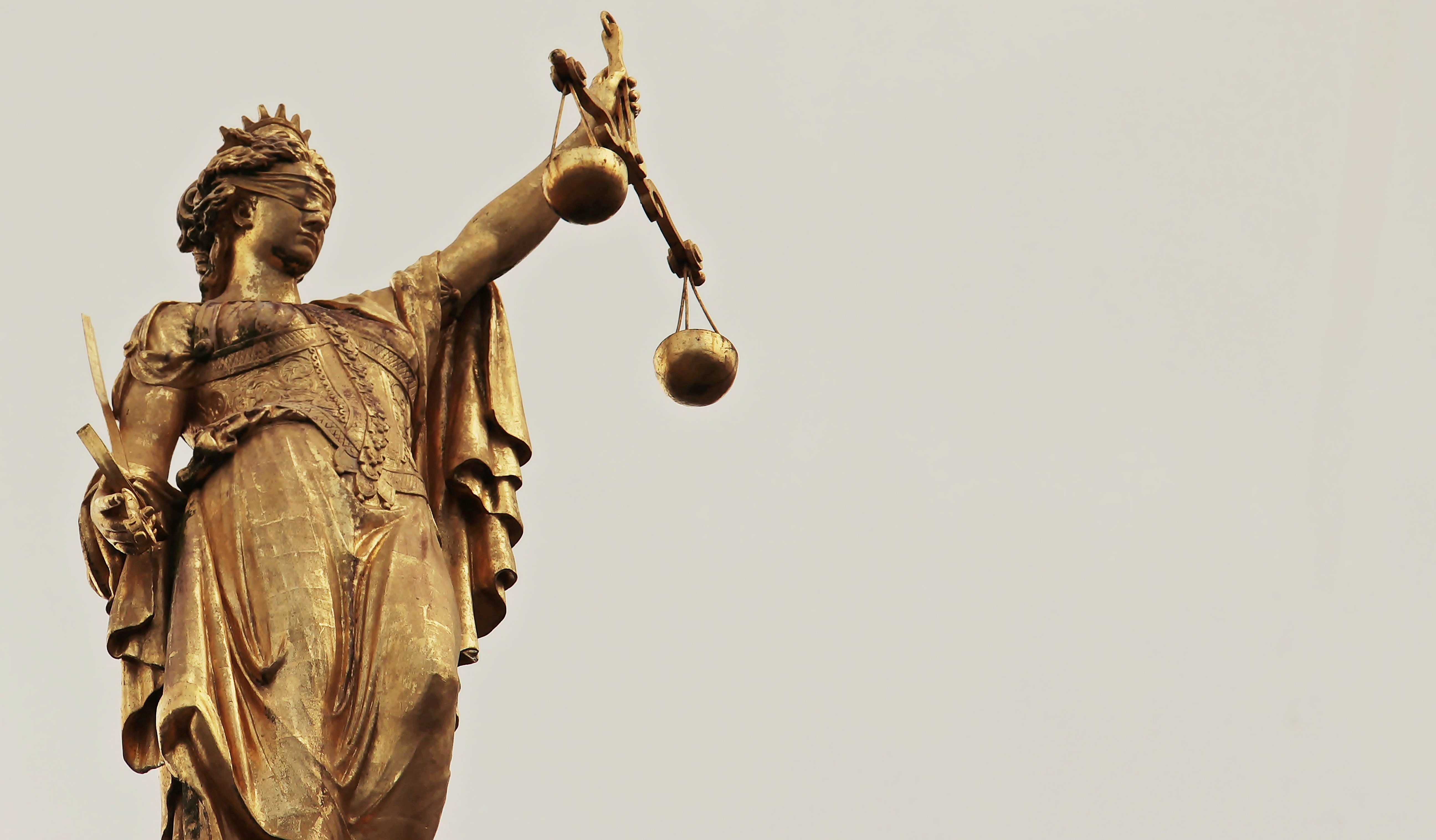 A statue of Lady Justice, Justitia. She is blindfolded and holds a balance and a sword.