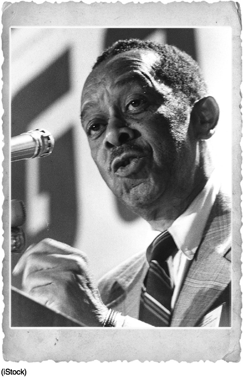 Photo of Kenneth Clark speaking into a microphone.
