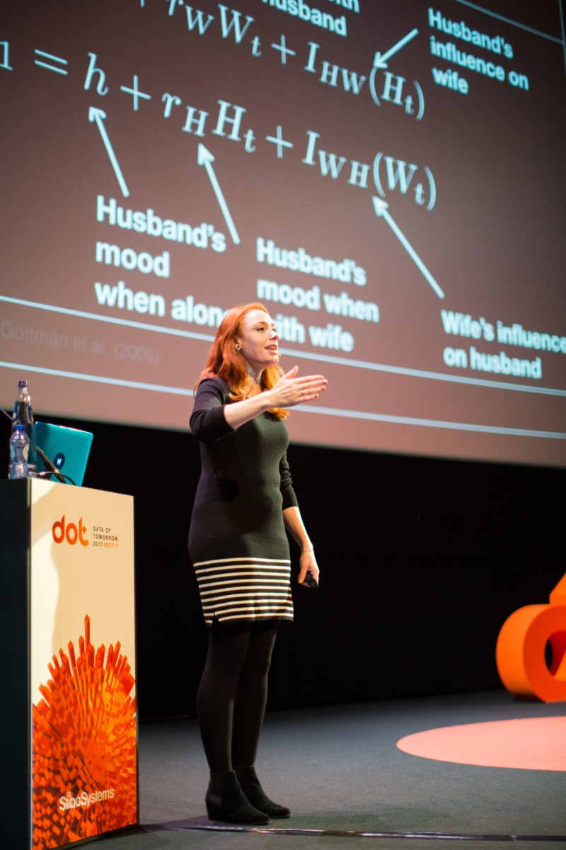 Hannah Fry standing on a stage with a large presentation aid behind her.