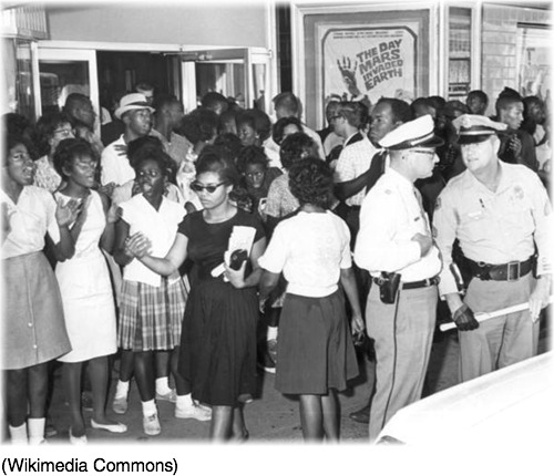 Photo of a Civil Rights demonstration in front of a segregated theater in Tallahassee in 1963. At the front, wearing a dress and sunglasses, is Patricia Stephens.