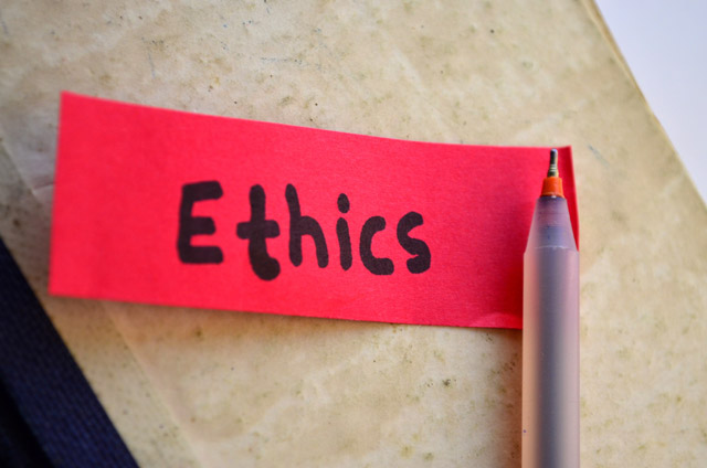 A pen with a red piece of paper labelled Ethics.