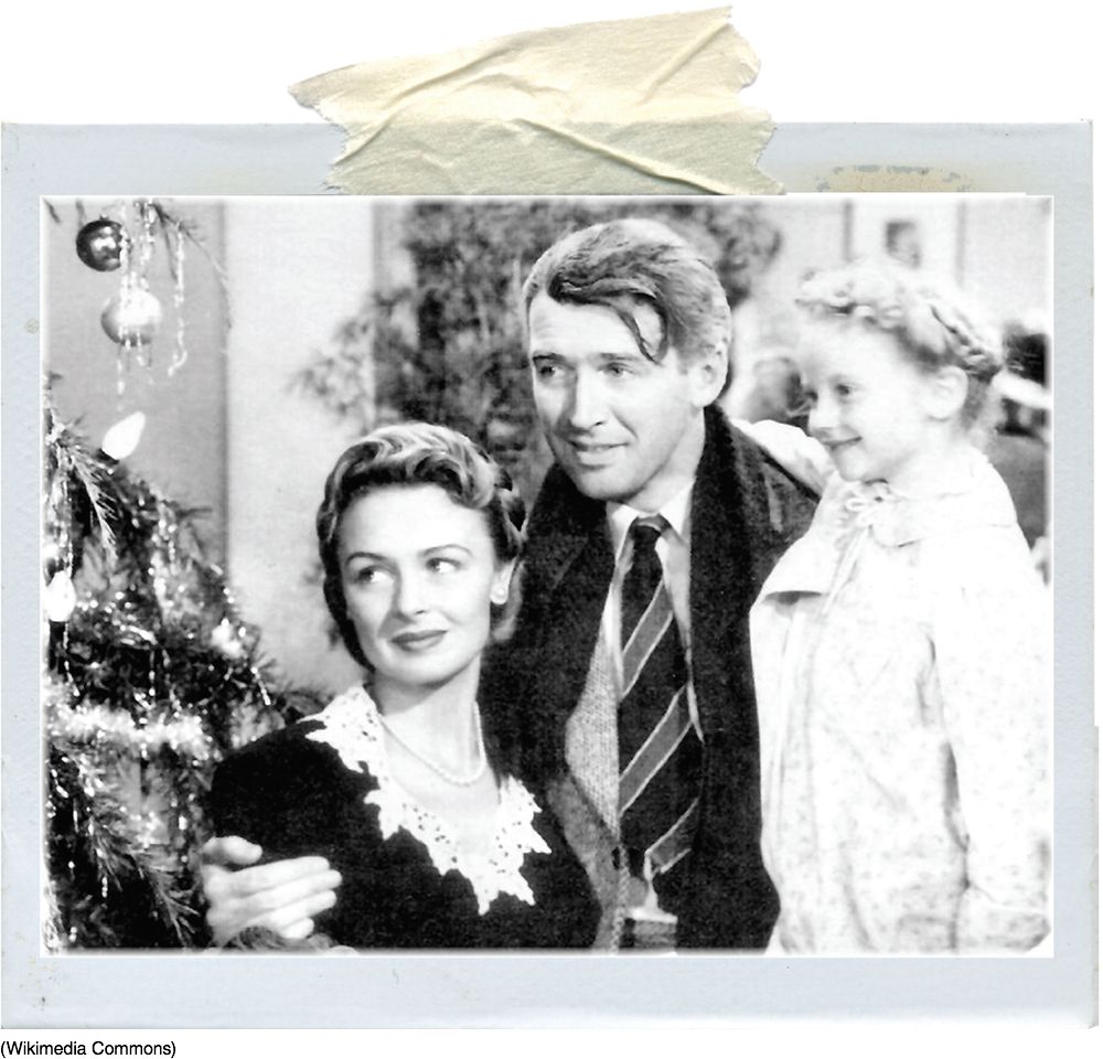Image of a scene from the movie It's a Wonderful Life, in which the main character has his arms around his wife and child as they look happily upon the Christmas tree.
